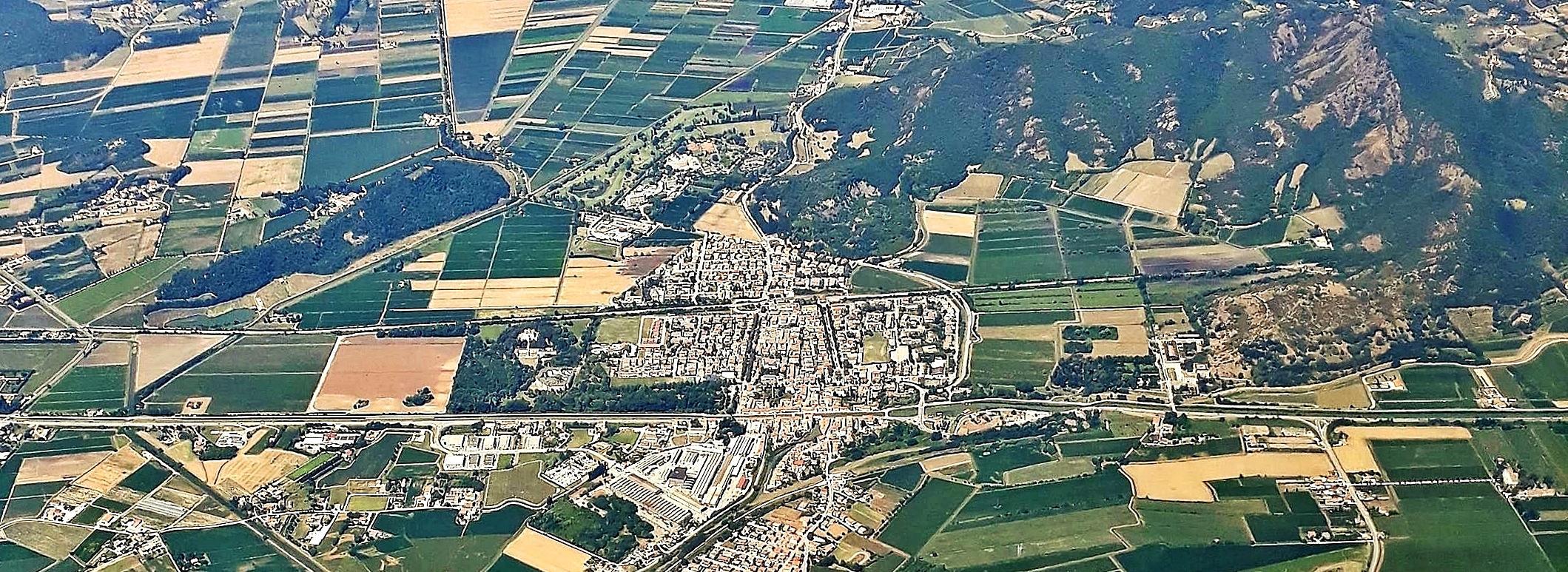 La foto aerea mostra l'abitato di Battaglia Terme, diviso dal canale e dalla ferrovia in tre parti.