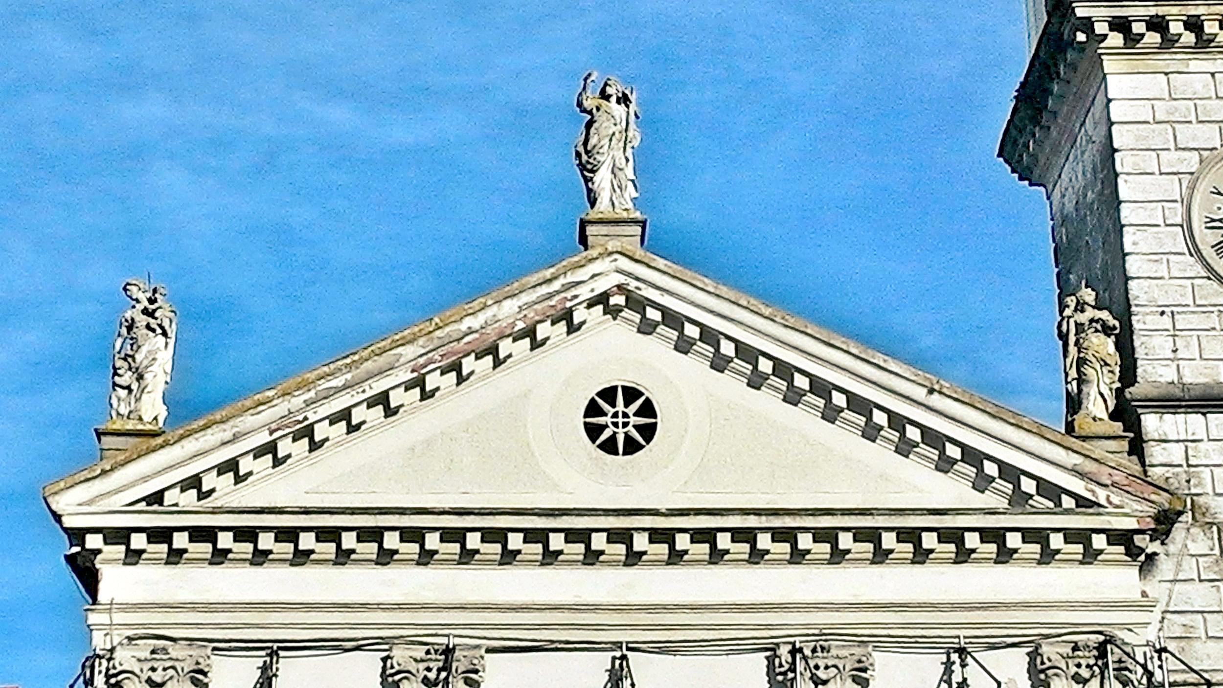 Facciata della vecchia chiesa di Battaglia Terme, il timpano con le sculture che rappresentano le Virtù teologali.