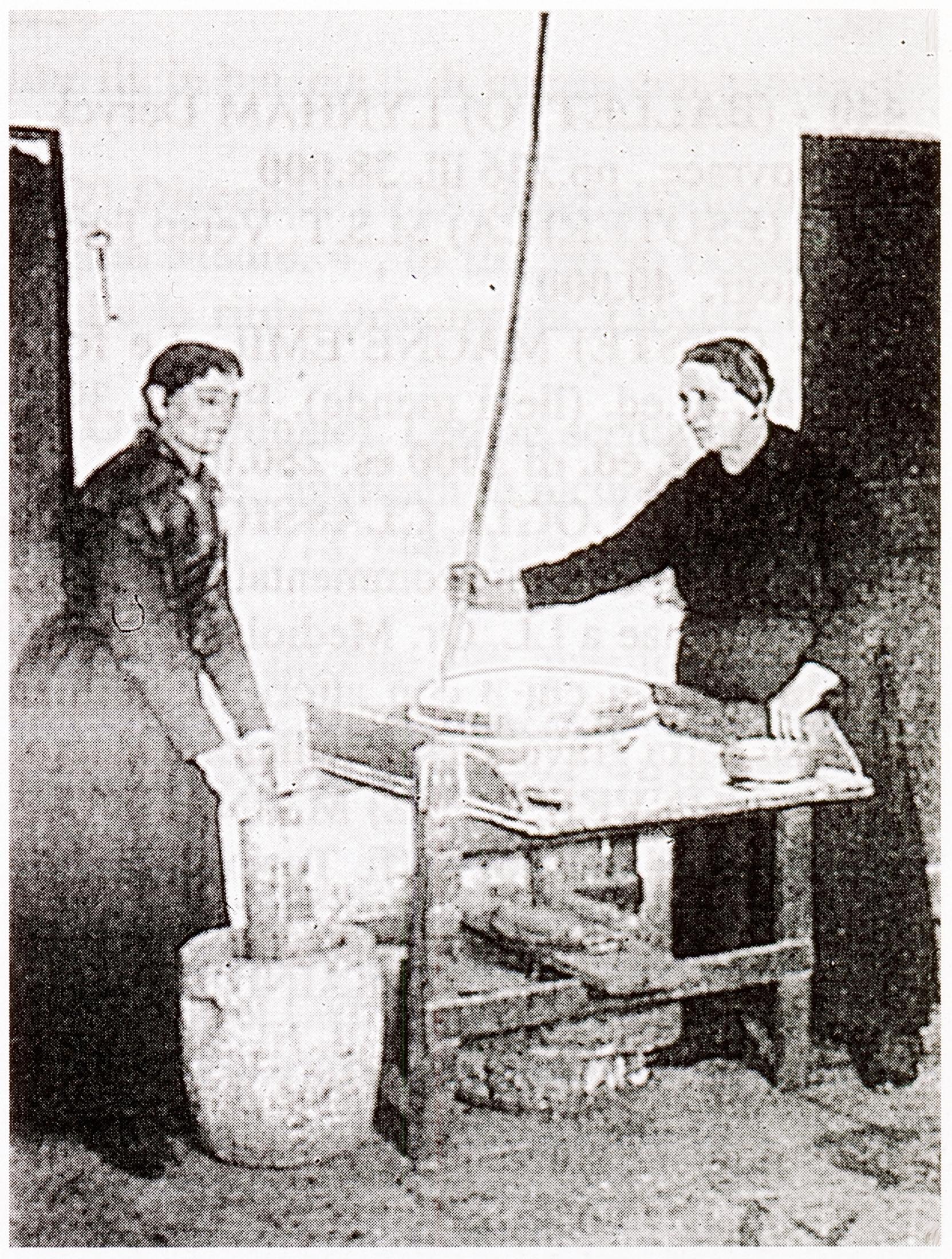 Dignano d'lstria, 1929. Due donne alle prese con un mortaio e una macina manuale.
